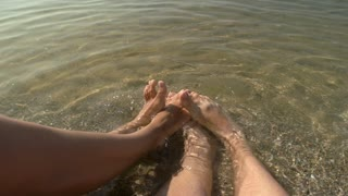 Legs of couple in water. Feet on the shore.