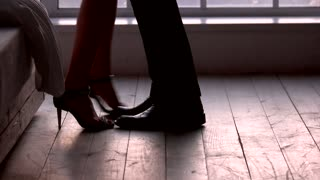 Legs of couple on floor. Man and woman in bedroom.