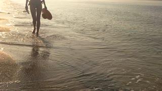 Legs of girl walking, seashore. Waves and wet sand.