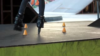 Legs of person on rollerblades. Rollerblader and slalom cones, motion.