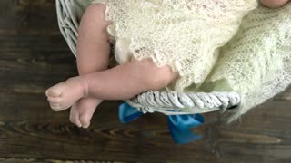 Legs of small child. White basket with baby.