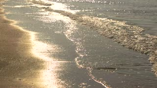 Legs of woman running, seashore. Water sparkling under sunlight. Escape to the sun.