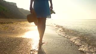 Legs of woman walking, beach. Barefoot lady near water.