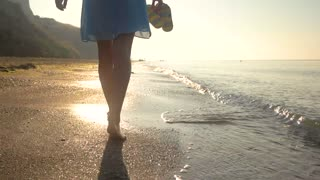 Legs of woman walking, seashore. Person carrying flip flops.