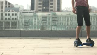 Legs on hoverboard. Person riding gyroscooter city background.