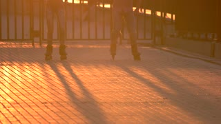Legs on rollerblades in motion. People rollerblading and sunlight. Great idea for active date. Keep your balance.