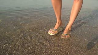 Legs walking in slow-mo, seashore. Female feet in flip flops. Sunny summer day.