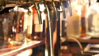 Light beer pouring out of tap. Flowing down beer foam.