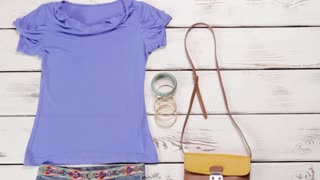 Light purple t-shirt with skirt. Plain female clothes on table. Denim skirt and bicolor purse. Clothing and set of bracelets.