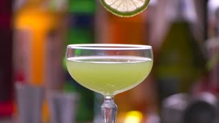 Lime slice slowly falls. Tongs hold slice of lime. Drink served at the restaurant. Fresh kiwi daiquiri at bar.