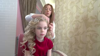 Little blonde girl, hair salon. Female hairdresser and a kid.