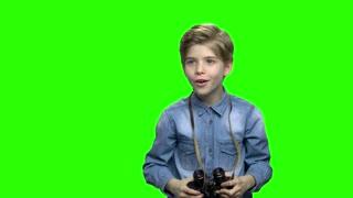 Little boy in denim jacket observing locations using binoculars. Green hromakey background for keying.