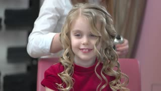 Little girl at hairdresser smiling. Beautiful child with curly hair.