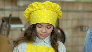 Little girl cooking. Smiling child in chef uniform.