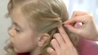 Little girl, hands of hairdresser. Face of child, side view.