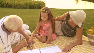 Little girl is drawing outdoors. Elderly people on grass near river with granddaughter. Art therapy concept.