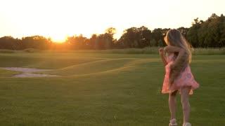 Little girl is running on green grass. Young girl running away, summer nature background. Little girl outdoors, sunset.