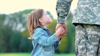 Little girl playing with father's hand. Daugther of soldier military daddy.