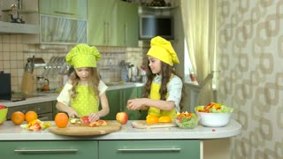 Little girls cutting fruit. Oranges and apples.