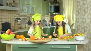 Little girls in the kitchen. Fruits on cooking table.