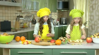 Little girls making salad. Greens and fruits. Kids cooking show.