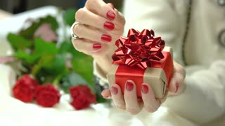 Little handmade gift box in female hands. Senior woman hands with red manicure holding gift box wrapped in craft paper and tied with red bow. Holidays and celebrations concept.