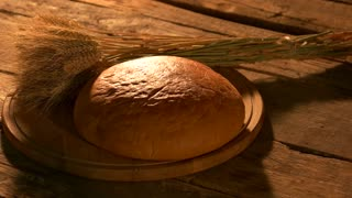 Loaf of round yellow bread and wheat ears. White bread loaf and bunch of wheat ears on round wooden board. Natural homemade pastry.
