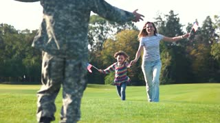 Long-awaited meeting of the military father with his family. Back side view soldier meet his family and start hugging. Summer lawn in the park.