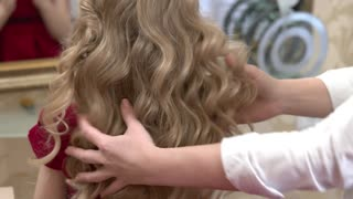 Long blonde curly hair. Hands of hairdresser, little girl.