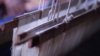 Loom. Women weave the fabric on the loom.