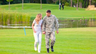 Lovely couple walking together in the park. Military army soldier with his girlfriend walking on vacation.