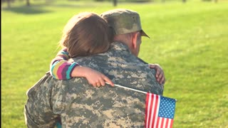 Lovely touching hugs of little girl with her military father came back. Daughter with USA background embracing her soldier daddy on park grass background.