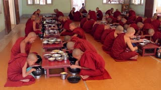 Lunch of the monks in the monastery. Religion Myanmar. Many monks in red robes. Meal of the monks. Religious people.