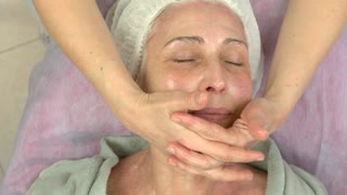 Lymphatic face massage adult woman. Mature female cosmetology.