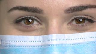 Macro view, female doctor eyes closing. Blinking eyelashes. Protective mask.