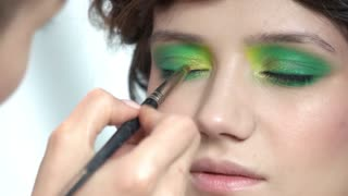 Makeup artist applying eyeshadow. Face of pretty girl, cosmetics. Model beauty tricks.