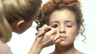 Makeup artist applying pink eyeshadow. Face of model isolated.