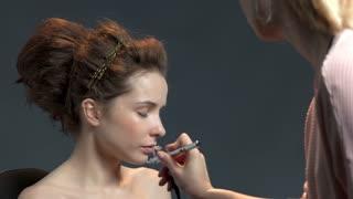 Makeup artist using airbrush. Beautiful young woman. Skin care secrets.