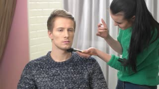 Makeup artist, young male model. Visagist working with handsome guy. Makeup tips for actors.