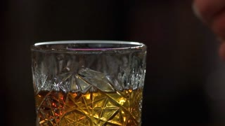 Making alcohol drink with fire. Barman set fire using match, close up, slow motion.