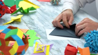 Making origami with black paper. Close up. Creating origami figures.