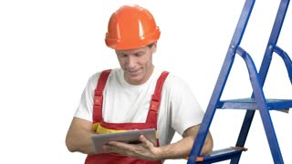 Male construction engineer using digital tablet. Smiling attractive constructor with protective equipment using pc tablet isolated on white background.