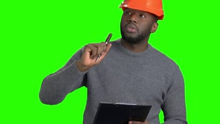 Male engineer checking new object. Afro american supervisor in hard hat making a note on clipboard on Alpha Channel background.