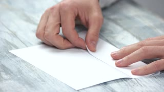 Male hands folding white paper sheet. Male person bend paper to make origami close up.