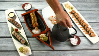 Male hands hold sushi plates. Kettle pouring liquid into bowls. Adding water to dry ice. Table with tasty japanese seafood.