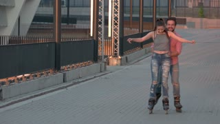 Man and woman are rollerblading. Smiling couple on inline skates. Cool idea for active date. Cheerful mood and good impressions.