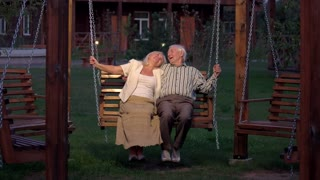 Man and woman outdoors, evening. Happy couple on porch swing. How to find love.