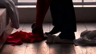 Man and woman undressing. Clothes of couple, bedroom floor.