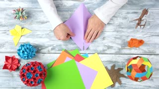 Man bend paper to make origami. Different origami figures on rustic wooden table. Paper folding workshop.