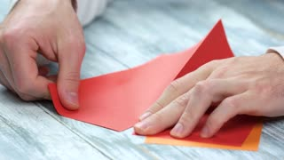 Man creating origami close up. Male hands dividing paper sheet in half. Paper folding lesson.